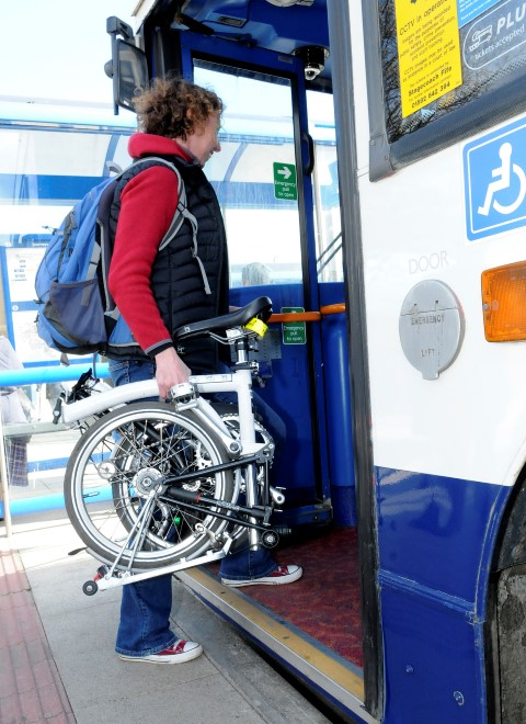 photo of woman getting on bus with fold-up bike